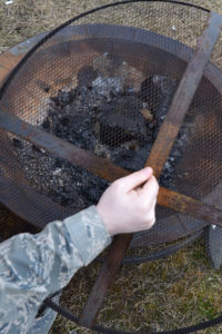 Man in military camouflage lifting fire pit screen